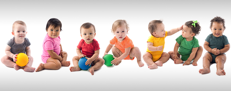 An image of babies and toddlers of various ethnicities wearing colorful onesies and sitting side by side in a long line.